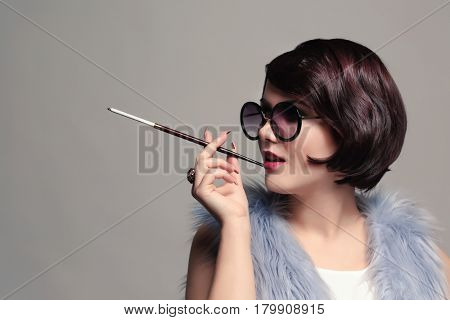 Young woman smoking with cigarette holder on grey background