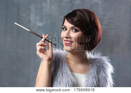 Young woman with cigarette holder on color background