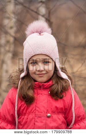 Portrait Of Happy Little Girl In Bright Red Jacket And Knitted Pink Cap On Spring Day Background Outdoor.