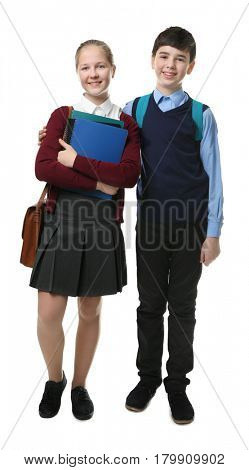 Cute boy and girl in school uniform standing on white background