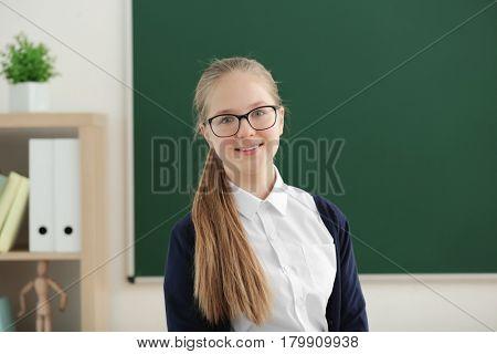 Cute girl standing near green school blackboard in classroom