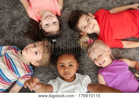 Cute little children lying on carpet at home