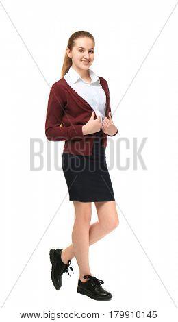 Beautiful schoolgirl in uniform standing on light background
