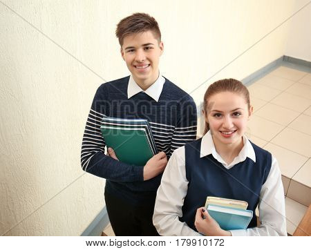 Cheerfully smiling pupils standing on stairs