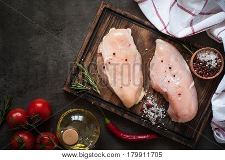 Raw chicken fillet on cutting board with sea salt pepper and rosemary. Food background cooking ingredients. Fresh meat.
