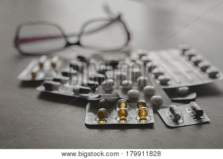 Pharmaceutical medicament. Pills and glasses in grey table