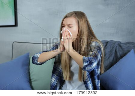Young woman blowing nose on tissue at home