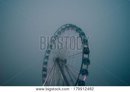 Mysterios inactive ferris wheel by heavy fog evening