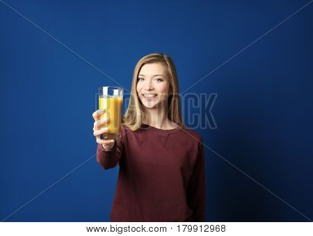 Beautiful young woman with glass of fresh juice on dark blue background