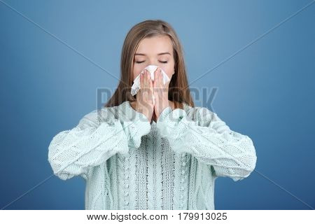 Young woman blowing nose on tissue against color background