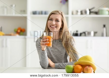Young woman with glass of fresh juice at kitchen