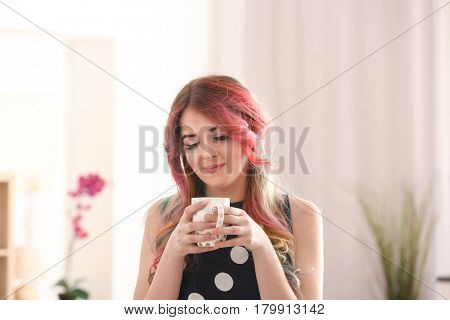 Young woman with colorful dyed hair resting  at home