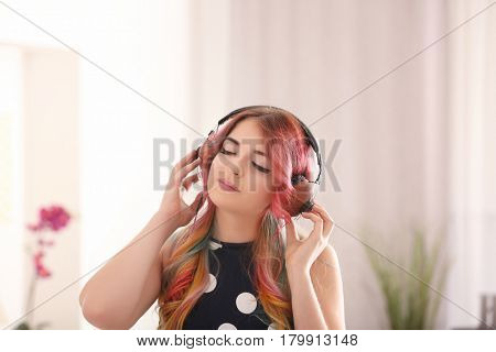 Young woman with colorful dyed hair listening to music at home