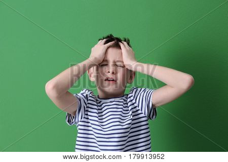 Cute boy suffering from headache on color background