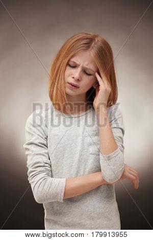 Cute girl suffering from headache on grey background