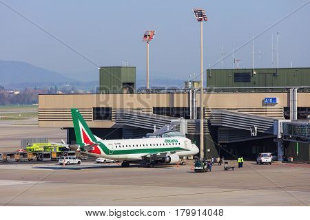 Kloten, Switzerland - 28 March, 2017: view in the Zurich airport with a Cityliner Embraer ERJ-175 of Alitalia at a terminal. Alitalia is the flag carrier airline of Italy.