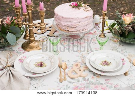 Wedding table. Vintage white plates with roses on a table with cutlery and glasses. Pink wedding cake with rose on the top on the banquet table