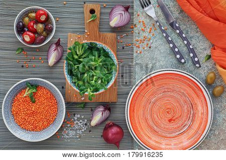Mediterranean snacks set. Green and black olives loaf of fresh multigrain bread corn salad and red onion over old wood background. Top view with space for text