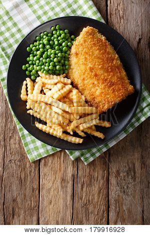 Traditional British Food: Fish And Chips With Green Peas Close-up On A Plate. Vertical Top View