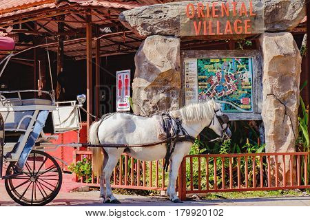 Langkawi, Malaysia - February 16, 2016: The pony for carrying the wagon at Oriental Village of Langkawi, Malaysia. Attractions for tourists. Vintage sign with old map of Oriental Village