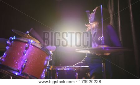 Attractive young girl rock musician - female drummer performing, telephoto