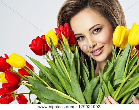 Closeup face of  beautiful happy woman with flowers in hands. Young attractive young girl holds the bouquet of red and yellow tulips