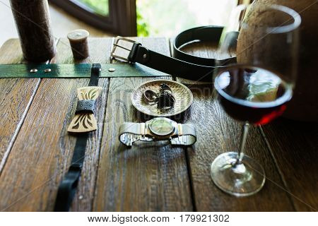 Wooden stylish necktie and other groom's accessories on a wooden table