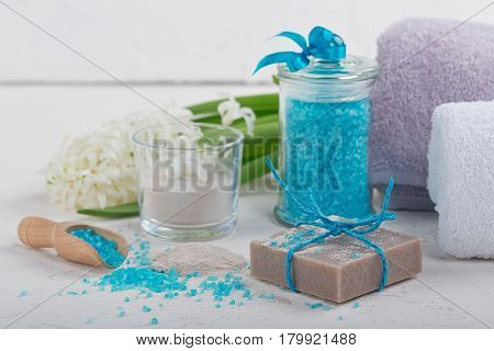 Cosmetic clay powder homemade clay soap and blue bath sea salt on white background. Face care body care and spa concept.