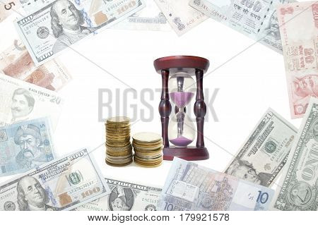 Hourglass and stacks of coins and banknotes of different countries. Concept on the topic of Finance and time.