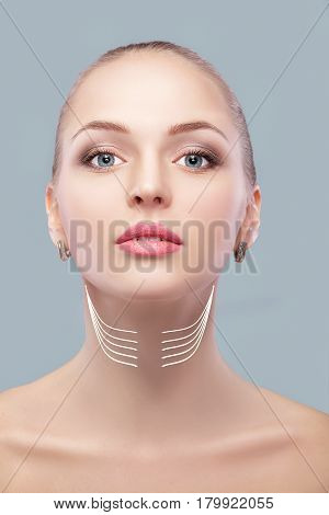 woman with arrows on her face over grey background. neck lifting concept. correction of double chin