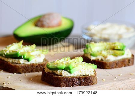 Hummus avocado sandwiches on a wooden board, avocado half, hummus in a glass bowl. Vegetarian sandwiches cooked with rye bread, avocado slices, hummus and roasted sesame seeds