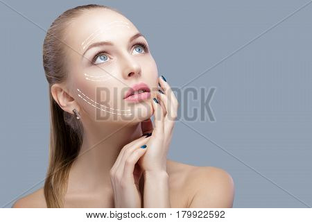 Spa portrait of attractive woman with arrows on her face  Face lifting concept. Plastic surgery treatment, medicine