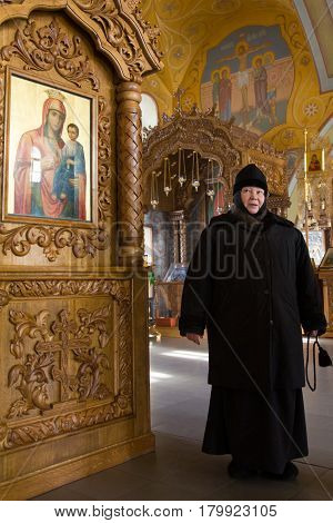 Kazan, Russia, 9 february 2017, golden domes in Zilant monastery - - a nun - Mother Sergiya in orthodox church near icons, vertical