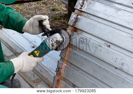 hands in rag gloves grinds steel structure for painting primer anti rust