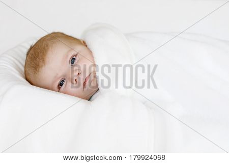Cute adorable newborn baby wrapped in colorful blanket, looking at the camera. Closeup of peaceful child, little baby girl sleeping. Swaddling as method for calm child