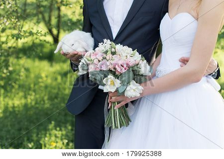 Wedding day. Bride holding in her hands a delicate wedding bouquet with white and pink tulips and pink small roses. Groom holding a white cute rabbit.