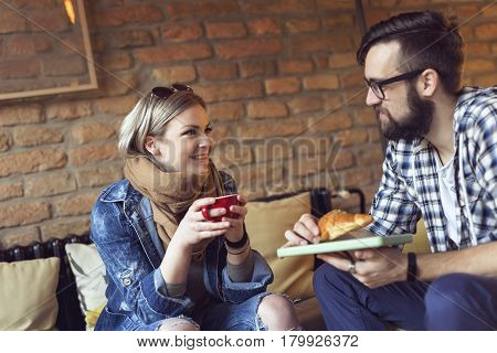 Two people sitting in a cafe having breakfast and enjoying a time spent with each other. Focus on the girl
