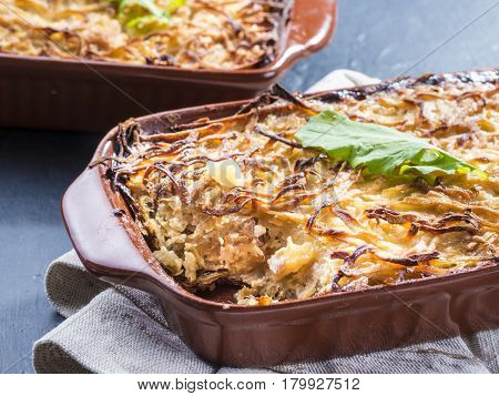 Close up view of appetizing potato casserole with fish, eggs and cream. Potato casserole in serving baking dish on dark concrete background