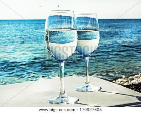 Two glasses of wine on beach near ocean at day