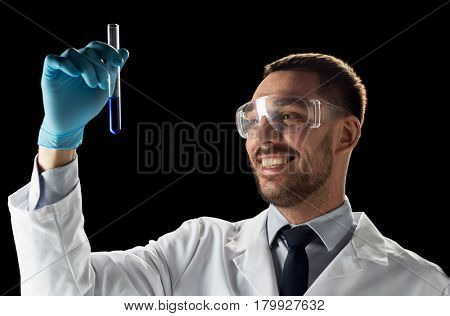 science, medicine, chemistry, research and people concept - young smiling scientist in safety glasses with test tube