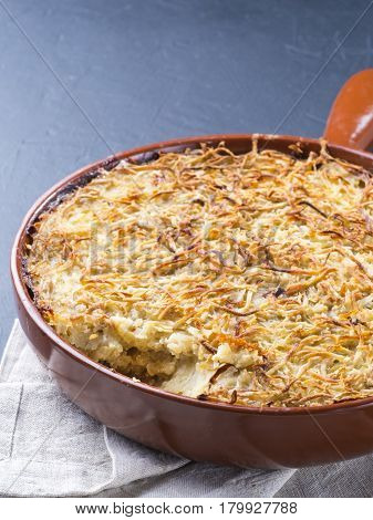 Close up view of appetizing potato casserole with fish, eggs and cream. Potato casserole in serving baking pan on dark concrete background