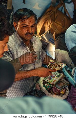 Unidentified man making foods for passengers inside Indian Railway local train on December 2012 in India. Indian Railways carries about 7, 500 million passengers annually.