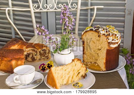 Typical italian flavorous home baked cakes for Easter: La Gubana with sophisticated stuffing and Panettone with candied flowers on the table covered for tea time. Horizontal. Main colors: white gray yellow brown.