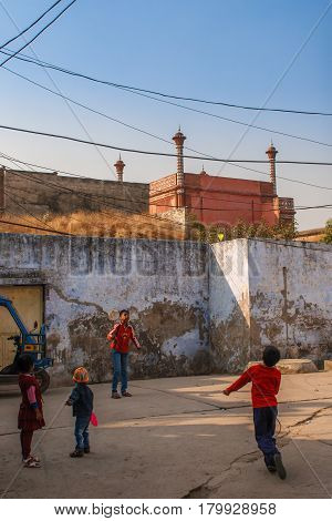 AGRA, INDIA - DECEMBER 2012: Taj Mahal fence and kids playing badminton near this wonder of the world. Siple indian life. One of the most famous building in the world. This mausoleum was built in 1631.