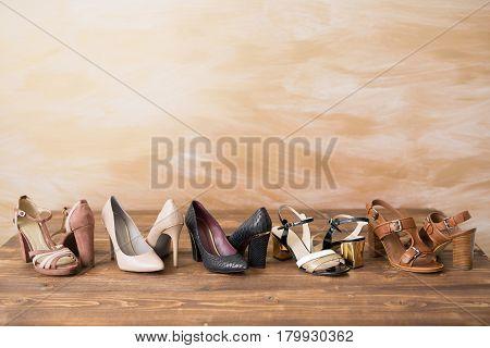 Diferent style woman's high heels on wooden floor
