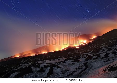 star trails on red lava river On Etna Park, Sicily