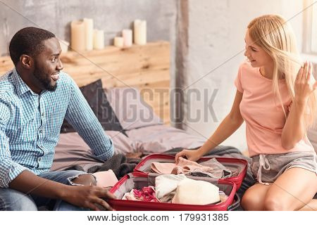 Packing luggage together. Lively amused international couple sitting at home and packing travelling case while expressing positivity