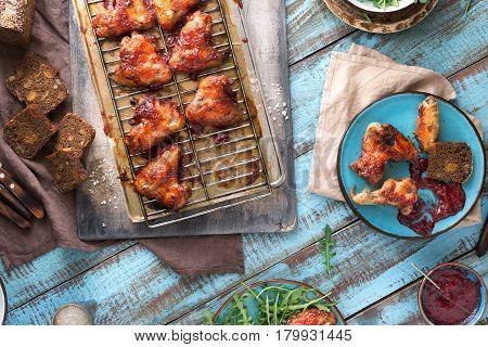 Homemade dinner party concept. Top view dinner table with chicken wings in cranberry sauce. Rustic style