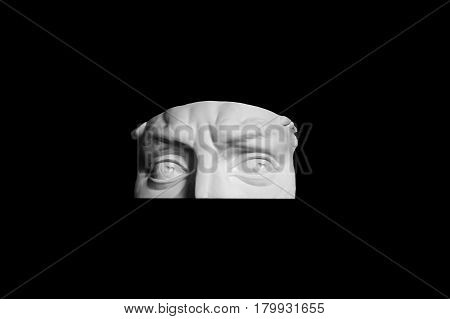 Plaster form parts of the upper part of human face. A fragment of the eye of the sculpture to visualize. Art sculpture isolated on black background. The face men white surround.