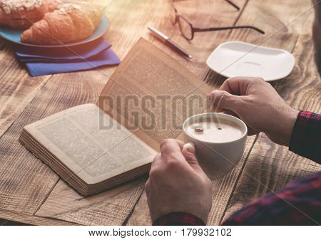 Man eating french breakfast and reading book while sitting at a wooden table